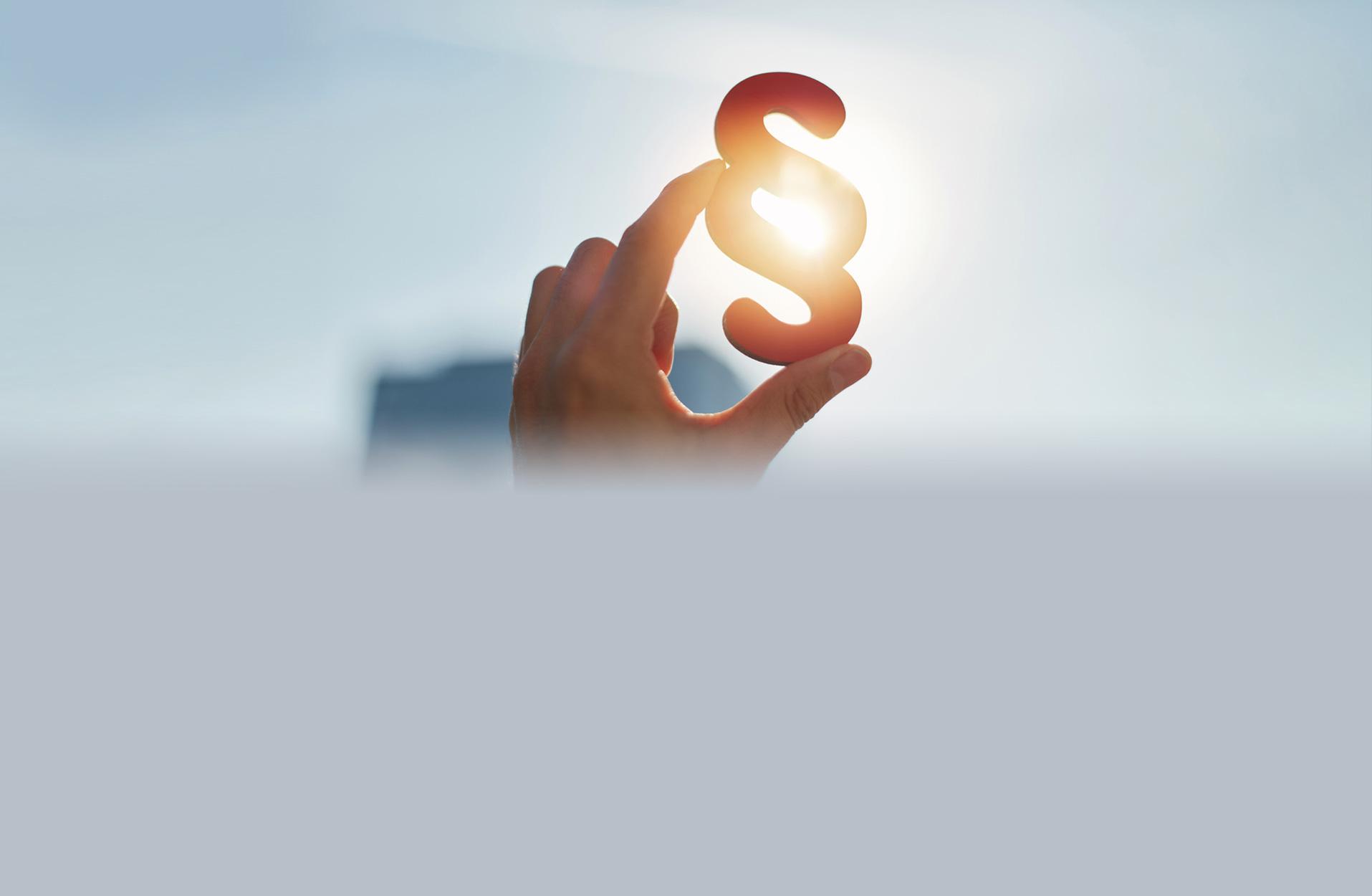 Hand hält Paragraphen Symbol in Sonne